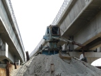 Small crane sitting on a pile of sand between two Delhi Metro viaducts, Mayur Vihar